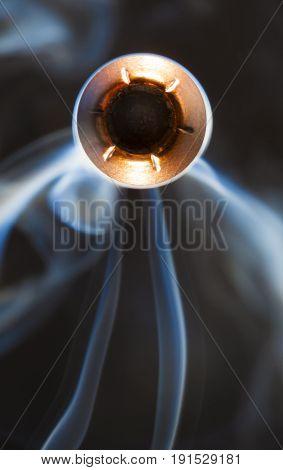 Smoke and hollow point handgun bullet coming at the camera