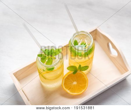 Lemonade With Fresh Lemon And Twig Mint With Drinking Straw On Wooden Tray
