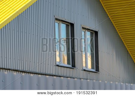 Corrugated metal facade. Pediment with two windows