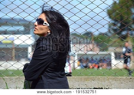 Woman with beautiful black hair looks at the soccer match from the edge of the playing field