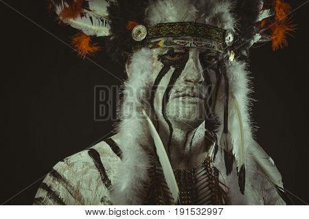 Chief Aboriginal, American Indian with plume of feathers, ax and war paintings