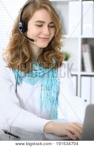 Call operator or business woman in headset working with laptop in the office.