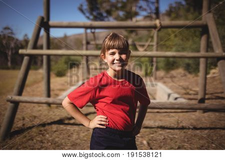 Portrait of happy girl standing with hands on hip during obstacle course in boot camp