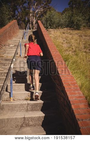 Rear view of girl running upstairs during obstacle course in boot camp