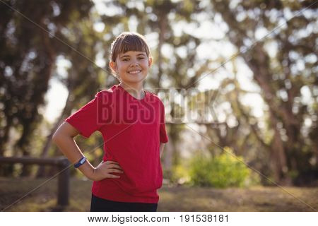 Portrait of smiling girl standing with hands on hip in boot camp