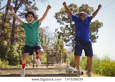 Happy friends cheering on obstacle during obstacle course in boot camp