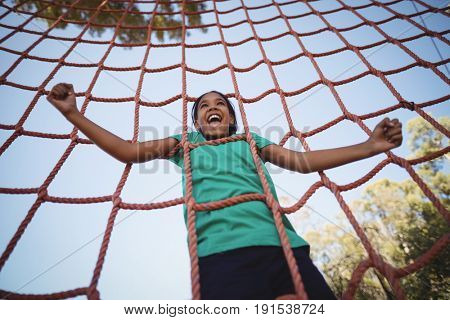 Happy girl cheering while climbing a net during obstacle course in boot camp