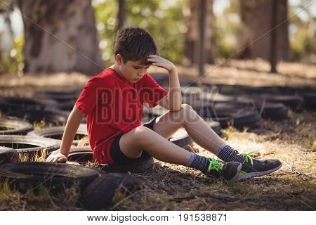 Sad boy relaxing on tyre during obstacle course in boot campboot, camp, boot camp, sunny, summer, park, kid, sportswear, athlete, athletic, obstacle course, determined, sitting, hand on forehead, poster