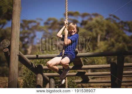 Portrait of smiling girl climbing rope during obstacle course in boot camp