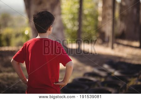 Rear view of boy standing with hands on hip during obstacle course in boot camp