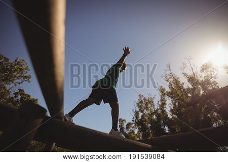 Boy exercising on obstacle during obstacle course in camp