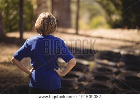 Rear view of girl standing with hands on hip during obstacle course in boot camp