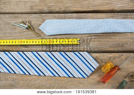 Overhead view of hand tools by necktie on wooden table