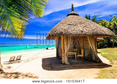 Relaxing tropical holidays. scenery with beach bungalow under palm tree. Mauritius island
