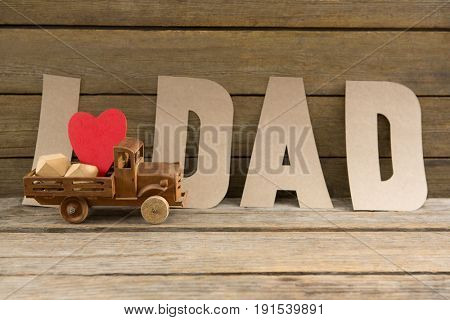 Close up of dad text by heart shape in toy truck on wooden table