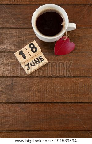 Overhead view of calender date and coffee cup with heart shape on wooden table