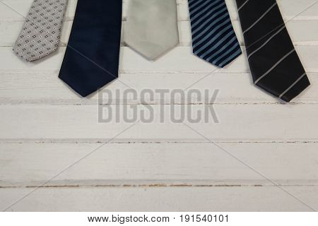 High angle view of neckties on white wooden table