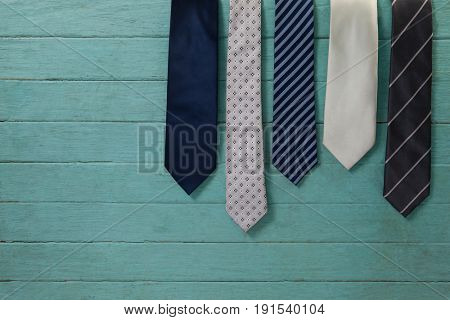 Various neckties hanging by green wooden wall