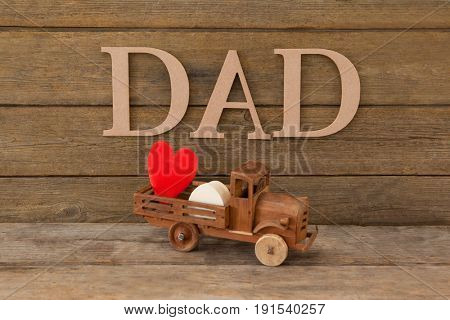 Dad text by heart shape in toy truck on wooden table