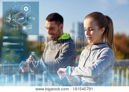 fitness, sport and technology concept - couple with heart-rate trackers exercising outdoors