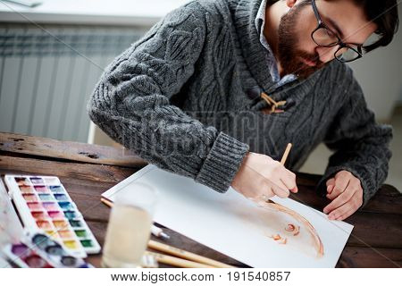 Serious painter drawing with watercolors by workplace