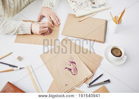 Human hands drawing pics of females with supplies around