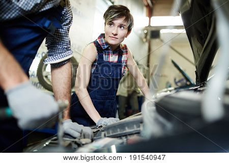 Young woman working with her master in car service