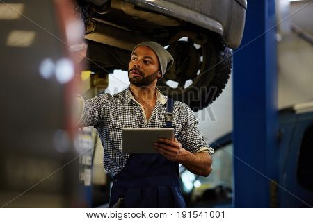 Repairman with touchpad making tire diagnostics