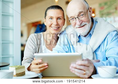 Affectionate couple of senior spouses spending leisure with touchpad