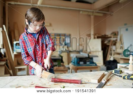 Boy with wood-chisel carving wooden plank