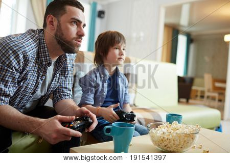 Serious man and little boy with consoles watching and playing video game