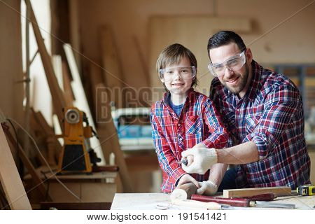 Little boy and man with chisel woodcarving together