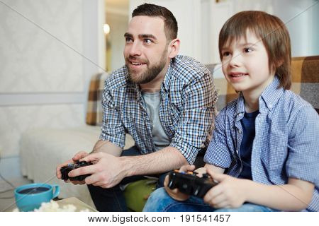 Little boy and young man with consoles spending weekend at home