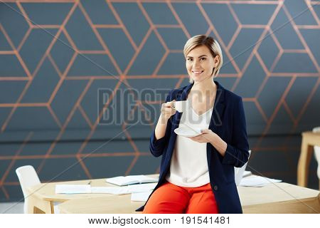 Smiling businesswoman with cup of hot drink
