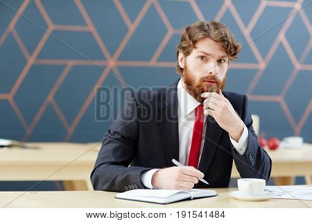 Businessman thinking of ideas and writing them down in notebook
