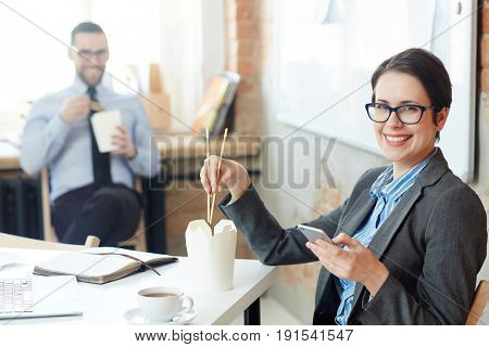 Happy businesswoman with chopsticks eating chinese food from take-out box