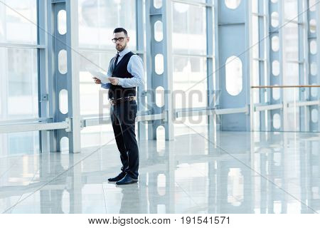 Portrait of contemporary successful businessman holding documents and looking at camera in hall of modern glass hall of office building, copy space