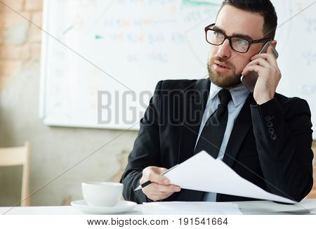 Modern trader speaking on mobile phone at work