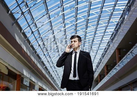 Portrait of successful confident businessman speaking by phone looking away under glass ceiling in modern office building