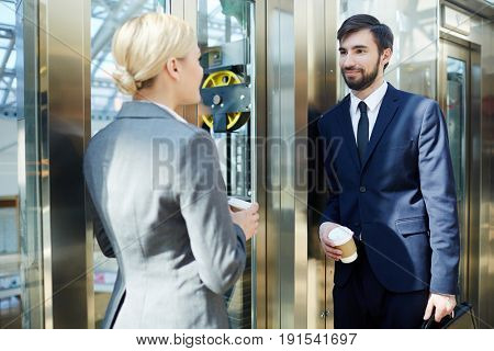 Portrait of two business colleagues, man and woman, chatting in elevator of modern office building