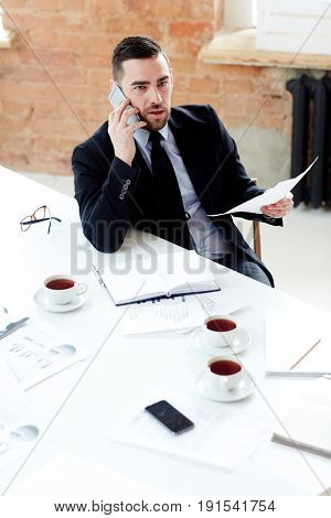 Businessman with paper calling his client while sitting in office