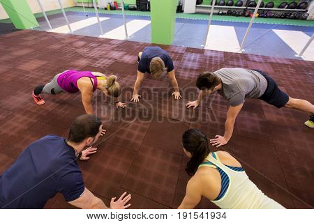 fitness, sport, exercising, training and healthy lifestyle concept - group of people doing straight arm plank in gym