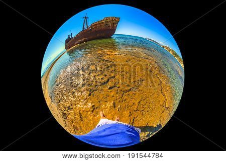 Transport world concept. Shipwreck at Agios Dimitrios near Gytheio in Laconia, Peloponnese, Greece. Legs of woman walking on desert land and wreck ship flying on roof the of the world. Fisheye shot.