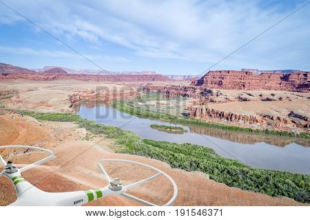 aerial view of the canyon of Colorado River near Moab, Utah, with a jeep trail and camp and drone propellers in picture frame