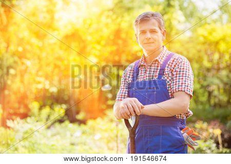 Portrait of confident gardener holding spade in plant nursery