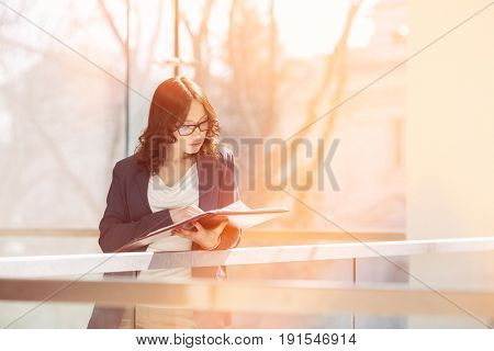 Businesswoman reading documents against railing in office