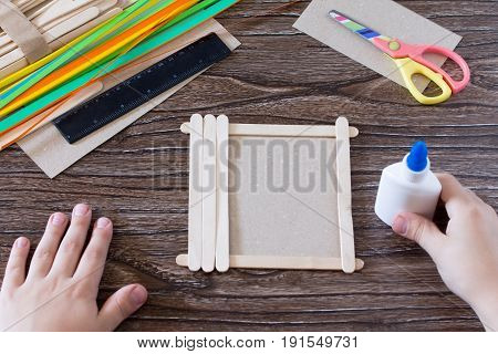 The Child Glues The Details To A Gift Photo Frame Made Of Wooden Sticks. Handmade. Project Of Childr