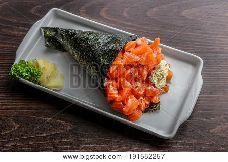 Huge and delicious Salmon and cream cheese philadelphia temaki on white place in a dark wooden background