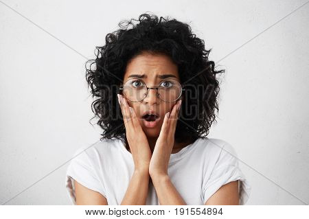 Anxious Woman With African Hairstyle, Smooth Cheeks And Big Dark Eyes Holding Her Trembling Hands On