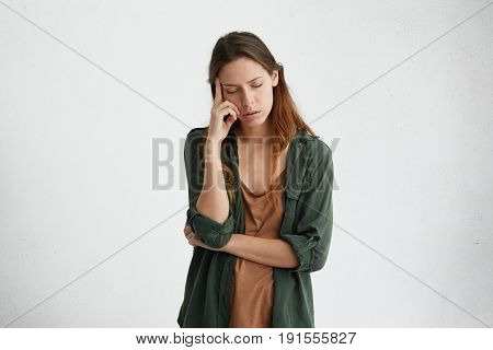 Exhausted And Tired Woman With Dark Hair Standing Against White Wall With Her Eyes Closed Holding In